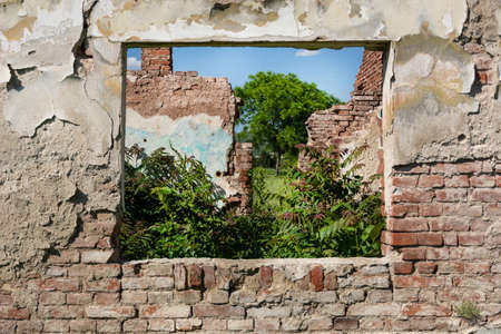 Ruins window and red brick wall of old the house without roof and grass growing from the floor. The house collapsed from catastrophe. Close up, selective focus