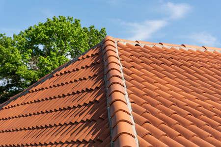 Orange Dachziegelmuster über blauem und bewölktem Frühlingshimmeltag und grünem Baum im Hintergrund. Das Dach auf dem modernen Hausbau. Nahansicht