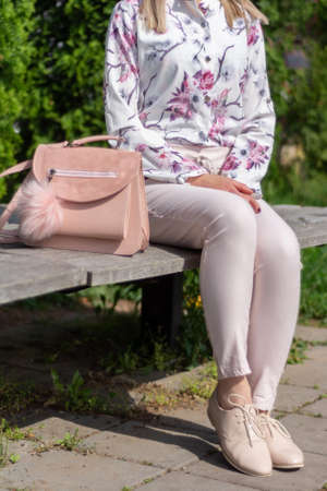 The fashionable girl sitting on a bench in a park next to a pink modern bag. A woman wears pink pants, beige lacquer shoes, and flowers design shirt. Vogue style concept. Close up, selective focu