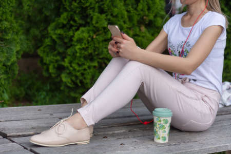 The fashionable girl working on a smartphone on legs and sitting on a bench in a park. A woman wears pink pants and beige lacquer shoes. Fashion and vogue style concept. Close up, selective focus Imagens