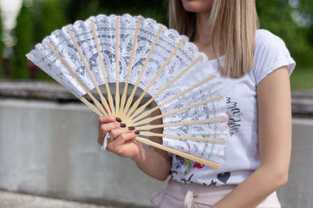 Ragazza alla moda con il ventaglio delle mani in una calda giornata estiva di sole seduto su una panchina del parco. Un ventaglio è un'eleganza e un materiale di pizzo. Concetto di moda e temperatura di calore. Primo piano, messa a fuoco selettiva