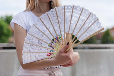 Girl with hands fan on a hot sunny summer day sitting on a park bench. A hand fan is an elegance and of lace material. Fashion and heat temperature concept. Close up, selective focus