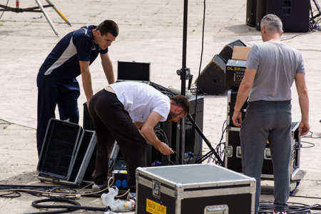 Nis, Serbia - May 25, 2019 Three technicians connect the music cables and the speakers outside. Preparing for a music festival in the city of Nis, Serbia, Europe. Close up, selective focus 報道画像