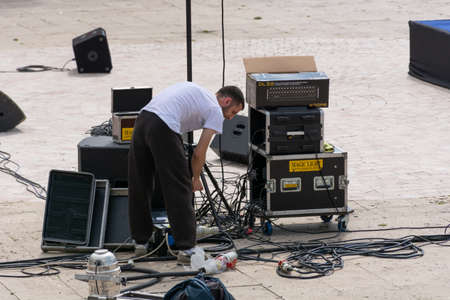 Nis, Serbia - May 25, 2019 The technician connects the music cables and the speakers outside. Preparing for a music festival in the city of Nis, Serbia, Europe. Close up, selective focus