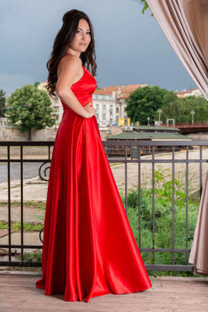 Beautiful girl in long red dress with hand on hips posing on the garden balcony on a wooden floor. Blurred cityscape, river and dramatic sky in the background. Fashion concept