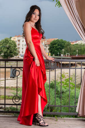 Beautiful girl in red dress holding dress and showing her leg and shoes on the garden balcony on a wooden floor. Blurred cityscape and dramatic sky in the background. Fashion concept