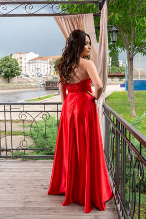 Pretty girl back in red dress with hand on hips posing on the garden balcony on a wooden floor. Blurred cityscape, river and dramatic sky in the background. Fashion and vintage concept
