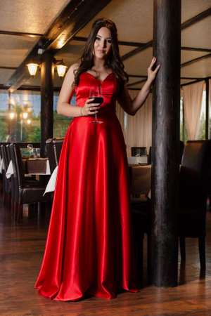 Beautiful young girl in a red dress holding wine glass and posing in the retro restaurant. Fashion and beauty concept. Close up, selective focus 写真素材