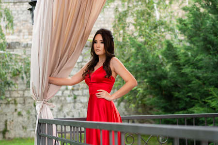 Girl in red dress posing and holds a hand on hips behind the fence on the balcony and curtains in the restaurant garden on a summer day. Fashion and beauty concept. Close up, selective focus 写真素材