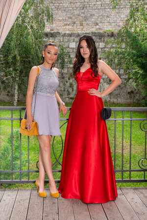 Two happy girls posing on a restaurant garden in front of the fence. Girls wear a red and gray elegant dress. Blurred wall background. Fashion concept. Close up, selective focus