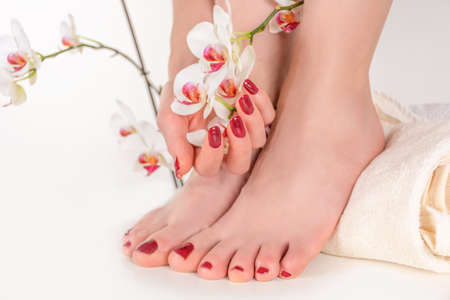 Young girl feet and hands with dark red polish color manicure and pedicure on a towel in the beauty salon and decorative orchid flower. Close up, selective focus