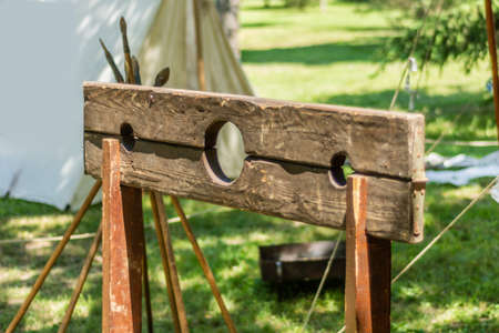 The pillory,  wooden frame usually mounted on a post where the criminal would place their head and hands through the holes. Medieval torture devices. Close up, selective focus