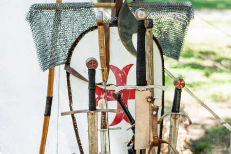 A medieval old group of swords and knights equipment. Close up of handles sword and blurred shield in the background. Medieval and historical concept. Selective focus.