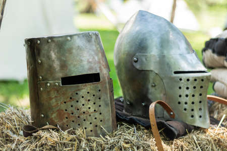 Knightly medieval metal two helmets on the stand. Old dark ages armor and equipment for knights head protection in battle. Historical and medieval concept. Close up, selective focus