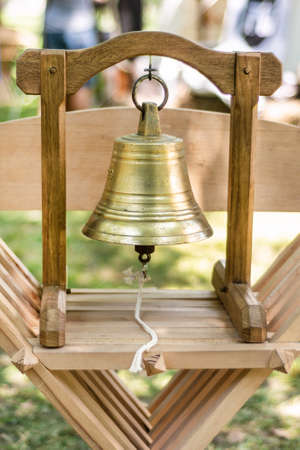 Medieval brass metal bell and wooden construction for hand use and ringing on wooden chair outdoor and blurred background. Historical and medieval concept. Close up, selective focus