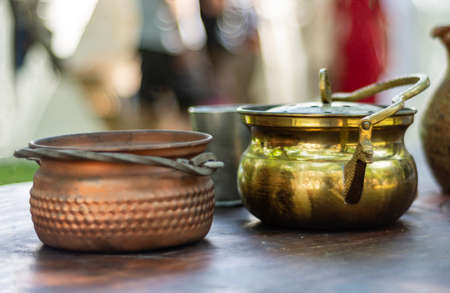 Medieval brass metal pot on old wooden desk and blurred background outdoor. Medieval or dark age food and drink dish concept. Close up, selective focus