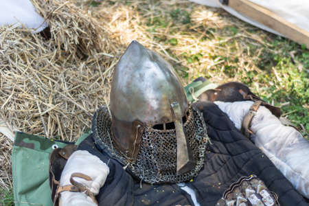 Medieval metal helmet on the floor. Old dark ages armor and equipment for knights head protection in battle. Historical and medieval concept. Close up, selective focus 写真素材