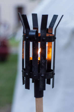 Medieval metal lantern burning in the night. Black iron lamp with the flame on the wooden stand on knights festival. Historical and medieval concept. Close up, selective focus 写真素材