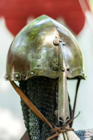 Medieval old metal helmet on the stand. Knightly armor and equipment for head protection in battle. Historical and medieval age concept. Close up, selective focus 写真素材