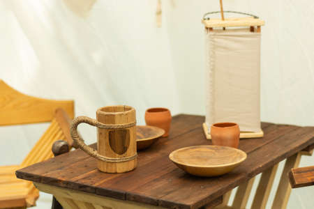 Medieval wooden beer mug and plates on the wooden desk. Very old wooden dishes and bowls for water or alcohol drink and food. Close up, selective focus