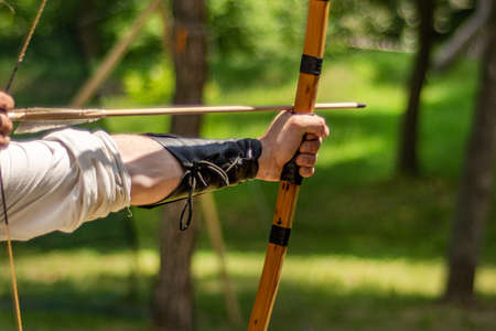 Archer hand holds his bow with an arrow and aiming at the target outdoor activity in forest. Medieval sport concept. Close up, selective focus 写真素材