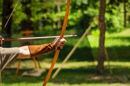 Man medieval archer hand holds his bow with an arrow and aiming at the target outdoor activity in the forest. Medieval sport concept. Close up, selective focus