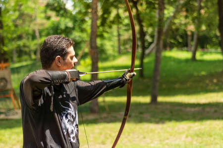 Nis, Serbia - June 16. 2019: Archer with bow shoot arrow in the forest on knight festival in a traditional suit. Bowman before shooting from a longbow. Close up, selective focus