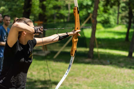 Nis, Serbia - June 16. 2019: Professional girl archer with bow shoot arrow in the forest on knight festival and tournament. Bowman before shooting from a longbow. Close up, selective focus 報道画像