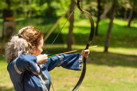 Nis, Serbia - June 16. 2019: Woman archer with bow shoot arrow in the forest on knight festival in a traditional suit. Bowman before shooting from a longbow. Close up, selective focus 報道画像