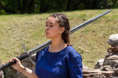 Nis, Serbia - June 15. 2019: Portrait of a medieval lady in a blue dress holding a big sword on the shoulder in front of a medieval ruins building and meadow. Close up, selective focus