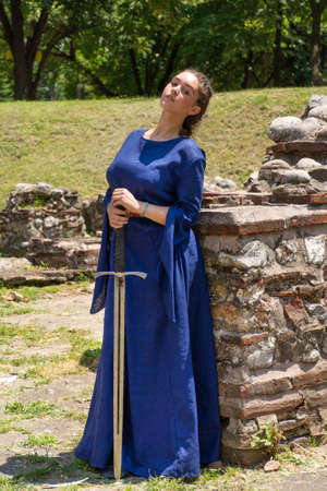 Nis, Serbia - June 15. 2019: Portrait of a medieval lady in a blue dress holding a sword in her hands in front of a medieval ruins building on a sunny day. Close up, selective focus