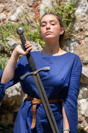 Nis, Serbia - June 15. 2019: Proudly medieval lady in a blue dress holding a big sword in hand in front of a medieval ruins building and meadow on a sunny day. Close up, selective focus 報道画像