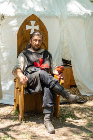 Nis, Serbia - June 15. 2019: Knight in folk costumes sits on a wooden throne in front of the tent and drinks wine on the international festival of knights. Close up, selective focus