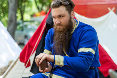 Nis, Serbia - June 15. 2019: Knight with a beard in a blue traditional suit sits in front of the tent and plays an old dice game on international knight festival. Close up, selective focus 報道画像