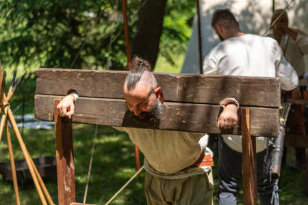 Nis, Serbia - June 15. 2019: Medieval prisoner in a wooden pillory of shame raped and tortured at an international knight festival. Close up, selective focus
