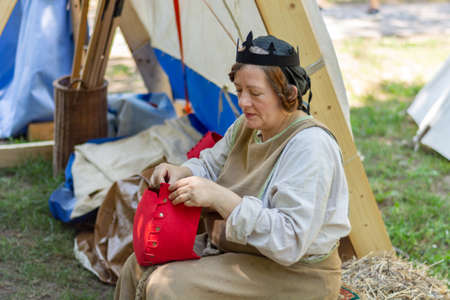 Nis, Serbia - June 15. 2019: Medieval woman in traditional costumes in front of a tent sewing a red hat at the knight festival. Medieval old crafts and skills. Close up, selective focus
