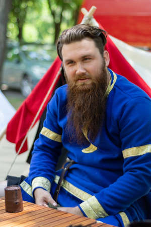 Nis, Serbia - June 15. 2019: Portrait of a knight with a beard in a blue traditional suit sits in front of the tent on international knight festival. Close up, selective focus 報道画像