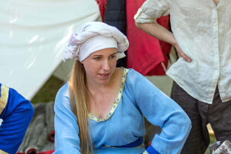 Nis, Serbia - June 15. 2019: Portrait of a medieval girl in a blue traditional dress and a white cap on the head of a knight festival. Close up, selective focus