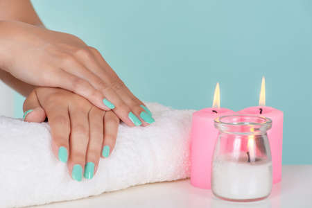 Young girl hands with a turquoise color nails polish on towel and decorative pink candles on desk isolated on soft blue background in studio. Manicure and beauty concept. Close up, selective focus 写真素材