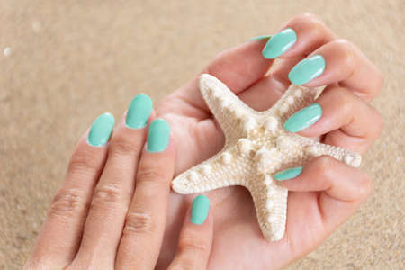 Beautiful female hands with a turquoise color nails polish holding starfish and sea sand in the background. Manicure and beauty concept. Close up, selective focus 写真素材