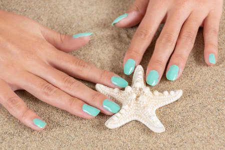 Gently female hands with a turquoise color nails polish holding starfish and sea sand in the background. Manicure and beauty concept. Close up, selective focus