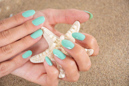 Girl hands with a turquoise color nails polish holding starfish and sea sand in the background. Manicure and beauty concept. Close up, selective focus
