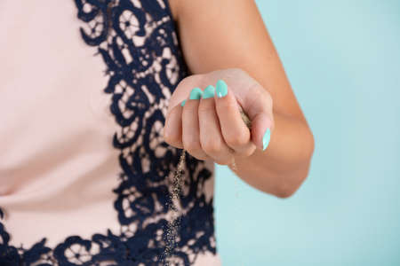 Woman hand with a turquoise color manicure holding sea sand and the sand leaking from the hand in the studio. Manicure and beauty concept. Close up, selective focus