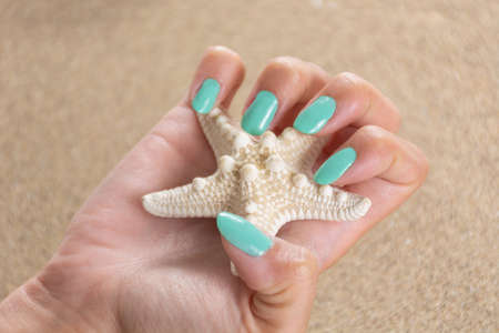 Young female hand with a turquoise color nails polish holding starfish and sea sand in the background. Manicure and beauty concept. Close up, selective focus 写真素材