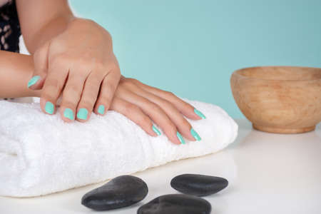 Young girl hands with a turquoise color nails polish on a towel and decorative stone on desk isolated on soft blue background in studio. Manicure and beauty concept. Close up, selective focus 写真素材