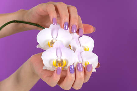 Young woman hand with a lilac color nails polish gel and beautiful orchid flower decoration on purple background in the studio. Manicure and beauty concept. Close up, selective focus 写真素材