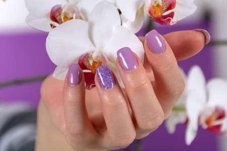 Female hand with a lilac color nails polish gel and beautiful orchid flower decoration on purple background in the studio. Manicure and beauty concept. Close up, selective focus