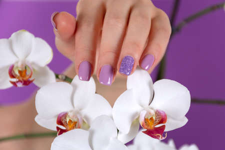 Girl hand with a lilac color nails polish gel and beautiful orchid flower decoration on purple background in the studio. Manicure and beauty concept. Close up, selective focus 写真素材