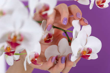 Young female hand with a lilac color nails polish gel and beautiful orchid flower decoration on purple background in the studio. Manicure and beauty concept. Close up, selective focus 写真素材