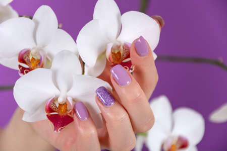 Young girl hand with a lilac color nails polish gel and beautiful orchid flower decoration on purple background in the studio. Manicure and beauty concept. Close up, selective focus 写真素材